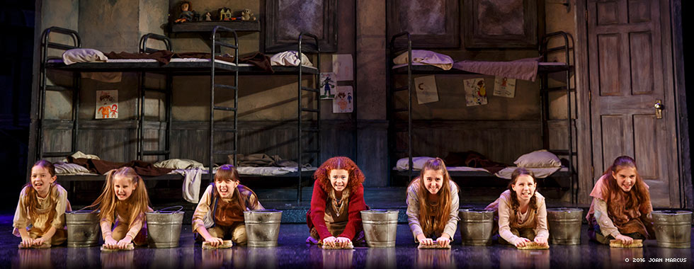 Seven child actors, with Annie in the center, sing a musical number while on their hands and knees scrubbing the floor.