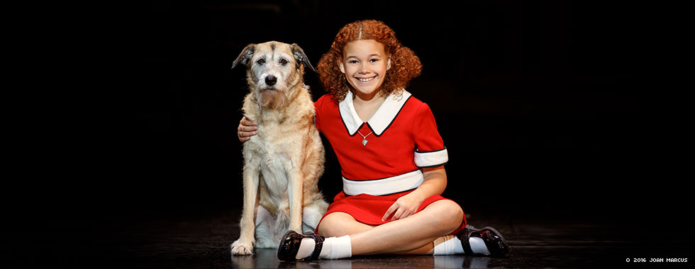 An actress portraying Annie smiles and sits cross-legged while she puts her right arm around Sandy the dog.