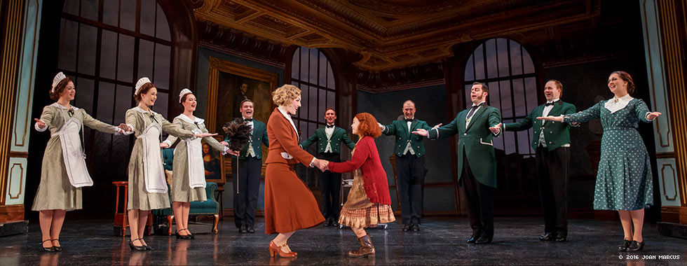 An actress portraying Annie smiles and holds both hands of an older actress while a staff of housekeepers and butlers with their arms outstretched surround them.