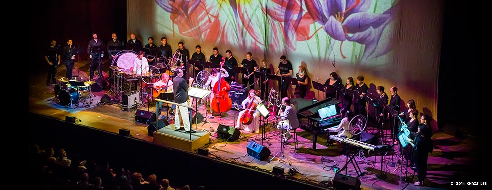 Chorus singers stand at the back of the stage behind Bang on a Can All-Stars and the ensemble's variety of stringed, percussion, and synthesizer instruments while a screen behind the musicians and singers show a painting of flowers.