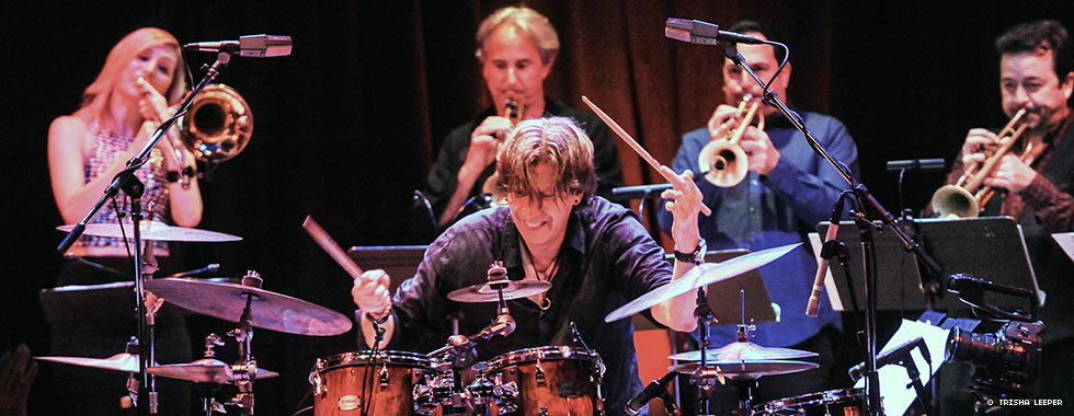 Drummer Tommy Igoe sits behind his kit and taps the cymbals while four brass musicians play behind him.