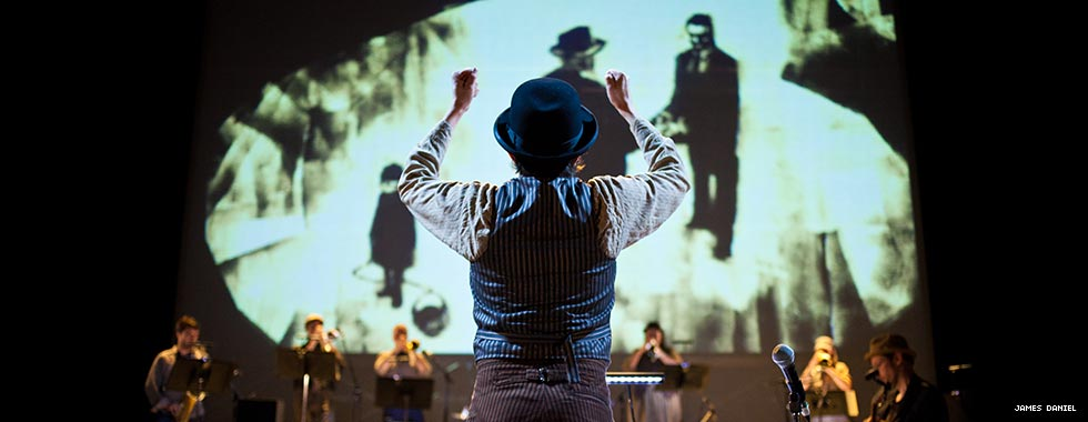Darcy James Argue stands with his back to the crowd as he leads his Secret Society jazz ensemble in a performance while an illustration of two men shaking hands and a boy looking downward appears on a screen behind the ensemble.