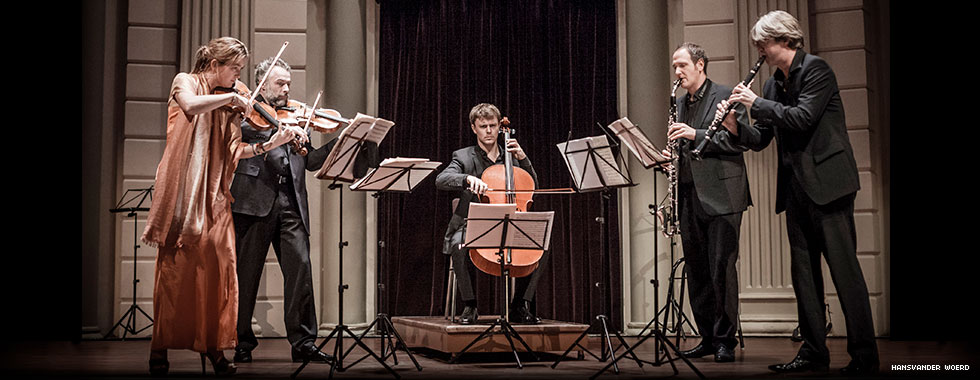 Four musicians, playing string and wind instruments, stand to each side of a man seated and playing a cello.