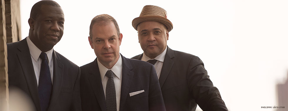 Three man in suits, with one wearing a homburg-style straw hat, look directly at the camera.