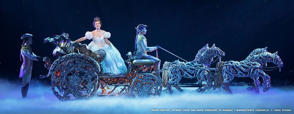 Cinderella smiles while she sits in a decoratively-lit horse-drawn carriage prop.