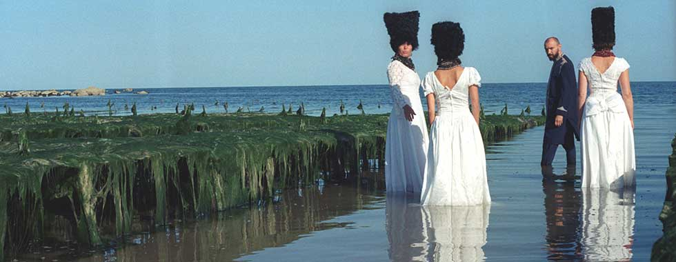 The members of DakhaBrakha, two of the musicians with their back to the camera and the remaining two looking over their shoulders to the photographer, wear traditional Ukrainian wedding attire and stand in seaside inlet with water reaching to their calves.