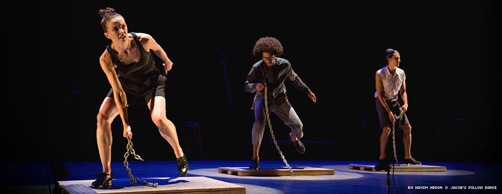 Three dancers stand bent over on boards as they extend a bent left leg back and drag a section of chain in on the floor with their right hands.