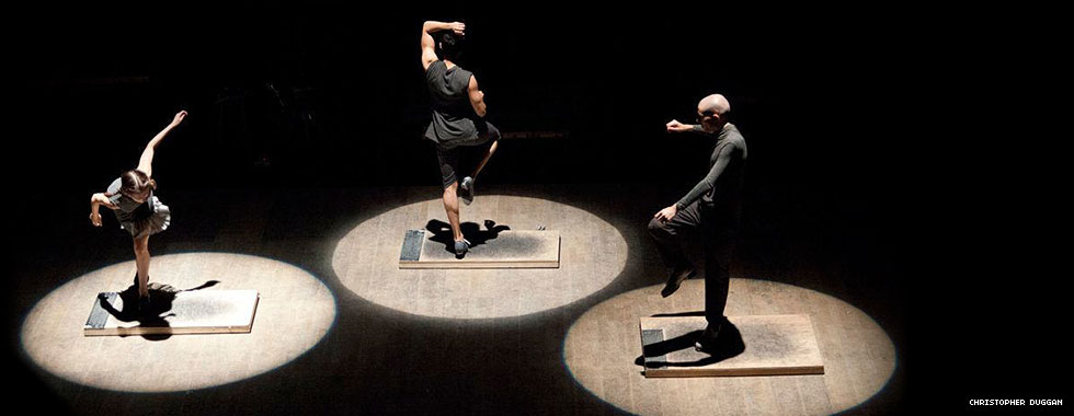 Spotlights illuminate three tap dancers each balancing on one leg on a board.