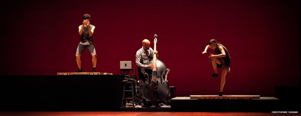 Two dancers on risers of different heights tap dance on each side of a cellist who plays his instrument.