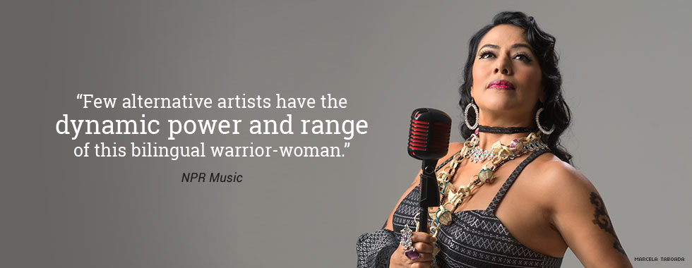 Lila Downs, wearing large baubles around her neck and on her fingers, holds a microphone in her right hand and looks up to the left.