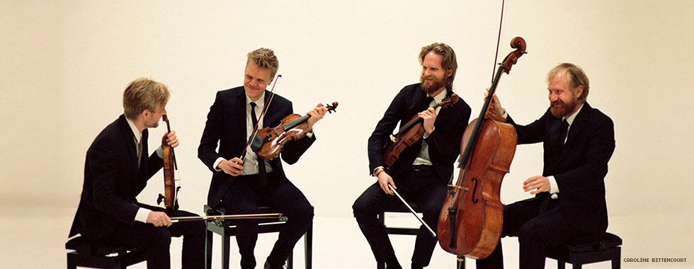 The members of the string quartet sit and smile at each other while holding their instruments and bows.