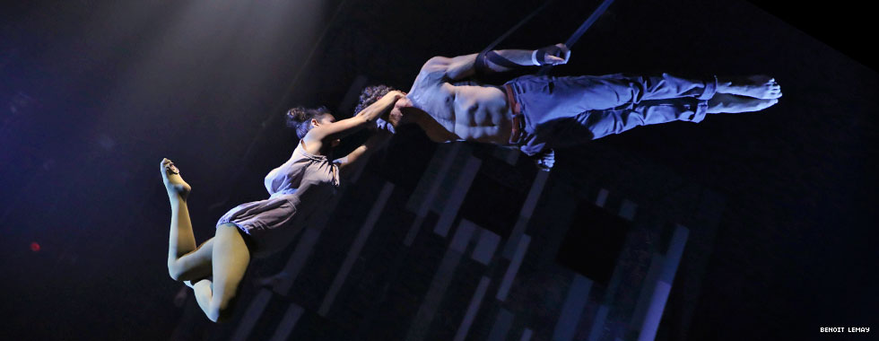 A female acrobat wraps her hands around a male acrobat's neck as he maintains a straight, rigid, feet-up form while suspended from aerial straps.