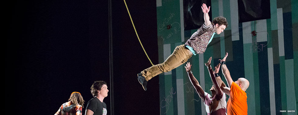 Two performers hold their hands up ready to catch a third acrobat who falls into their arms from a suspended rope.