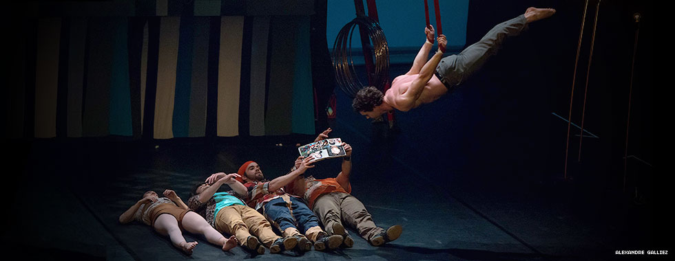 An acrobat hanging by his wrists from two suspended ropes swings low over four performers laying on the stage.