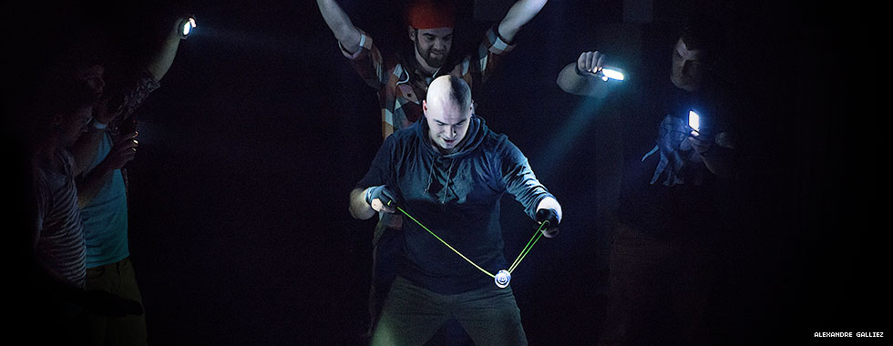 Circus performers hold flashlights on a performer who plays with a yo-yo.