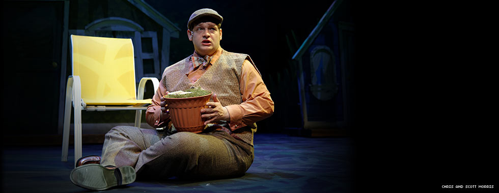 An actor wearing a vest, pressed slacks, and a beret sits next to a lawn chair and holds a flower pot.