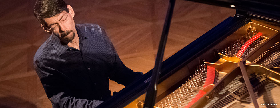 Jazz musician and composer Fred Hersch plays his piano with eyes closed and lips pursed while he leans to the right.