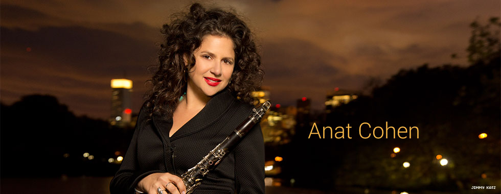 Anat Cohen, with a nighttime cityscape in the background, holds her clarinet with her right hand, leaning it on her left shoulder, while she smiles for the camera.