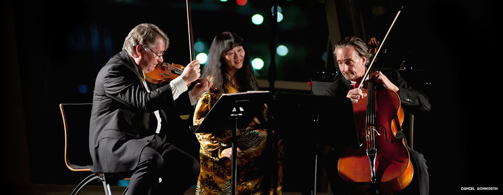 Violinist Philip Setzer and cellist David Finckel, both wearing tuxedos, look at their music stands and sit on either side of pianist Wu Han, who sits at her instrument and wears a traditional-style Taiwanese gown.