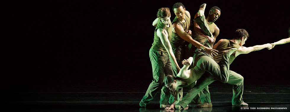 A tangled group of four dancers features one positioned face down with her right hand on the ground and held in place by another while two others extend their arms down to her back and another reaches out from the group to an unseen dancer with his right arm.