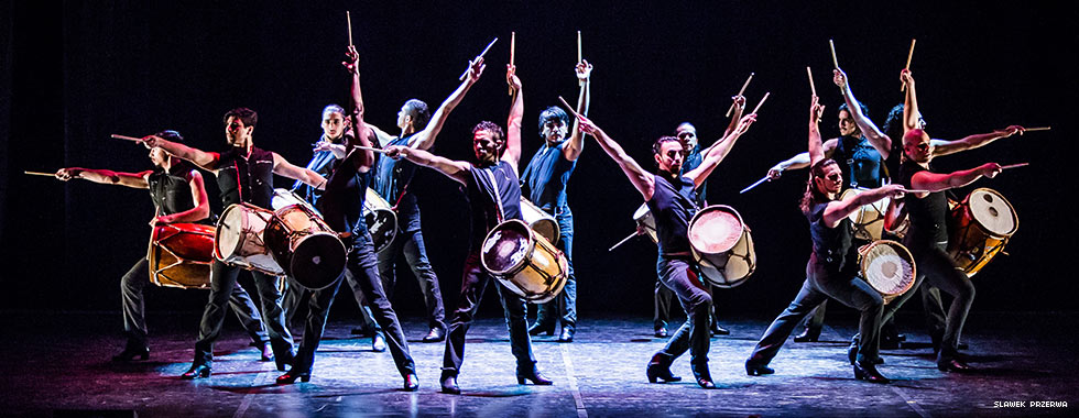 Twelve musicians each stand with their left arm raised and holding a drumstick while their drums hang from a strap around their shoulders.