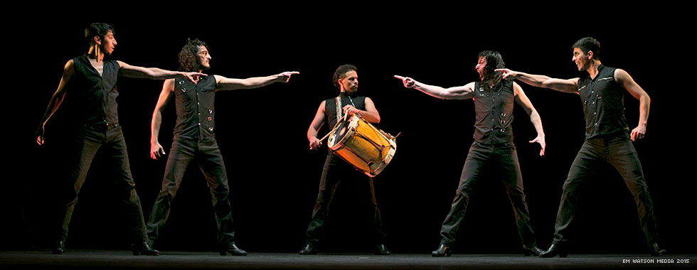 Four musicians point at a percussionist standing in the middle of them while he plays his drum.