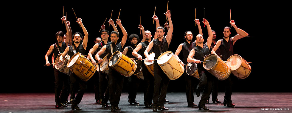 A group of musicians with drums strapped to their shoulders hold their arms above their heads or straight in front of them while they stand in a circle and look at the audience.