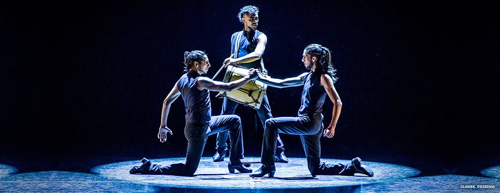A drummer stands in between two dancers while they kneel and lock their right hands together.