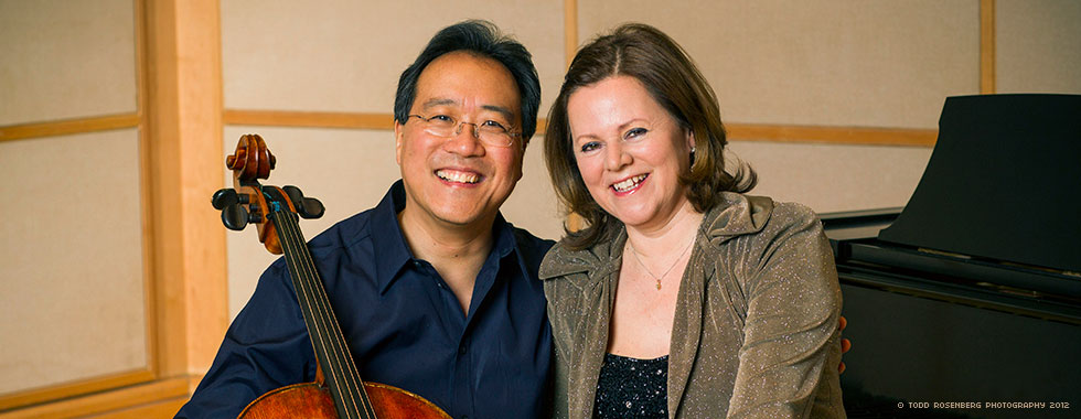 Yo-Yo Ma smiles while cradling his cello in his right arm and his left arm postured around a smiling Kathryn Stott.