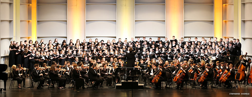 An orchestra performs in a semi circle around a conductor while members of a large chorus, each holding a songbook, stand on risers behind the musicians.