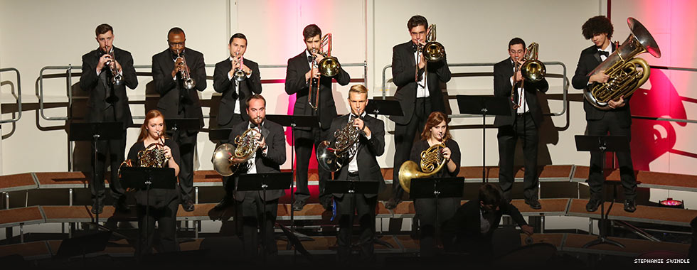 Eleven musicians playing a variety of brass instruments stand at their music stands in two rows.