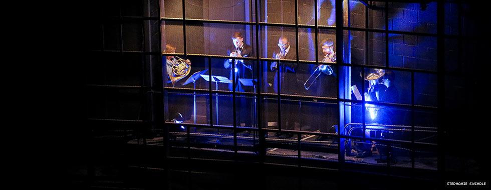 A light illuminates five brass musicians who perform in the mesh walls of Eisenhower Auditorium.