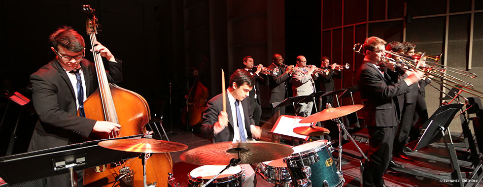 A cellist, drummer, and trombone and trumpet players look down at notes on stands in front of them while they perform.