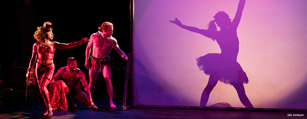 """Two shirtless male dancers and a female dancer dressed in leggings and asporty bodice watch a dancer dressed in a tutu posing behind a screen in Pilobolus' """"Shadowland."""""""