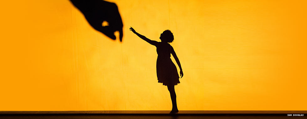 """The silhouette of a female dancer reaches up to a silhouette of a man's hand in a promotional photo for Pilobolus' """"Shadowland."""""""