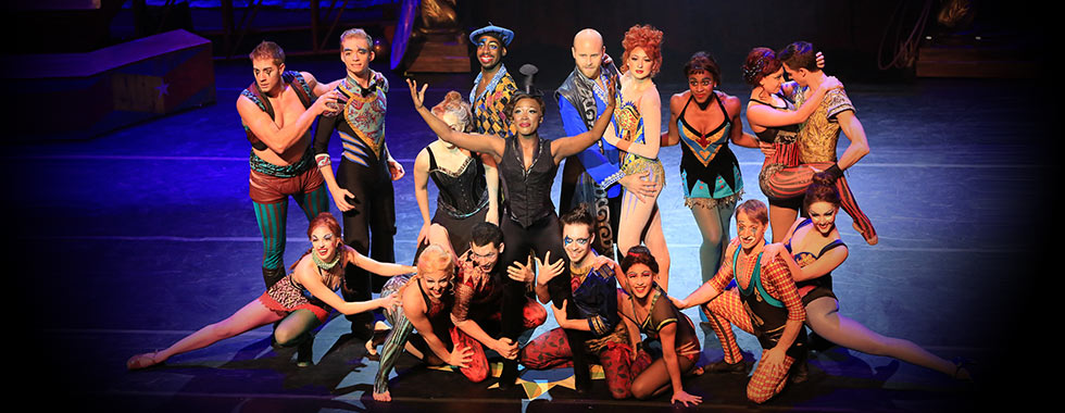 A diverse cast, featuring men and women kneeling and standing and wearing various styles of circus-themed tights and leotards, smile for the camera while they surround a woman holding her arms up.