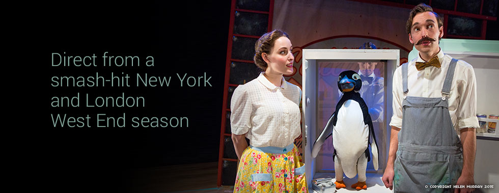 A woman stands next to a stuffed penguin and watches her male counterpart recite lines.