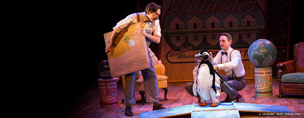 A man stands and holds a wooden box while another man crouches next to a stuffed penguin.