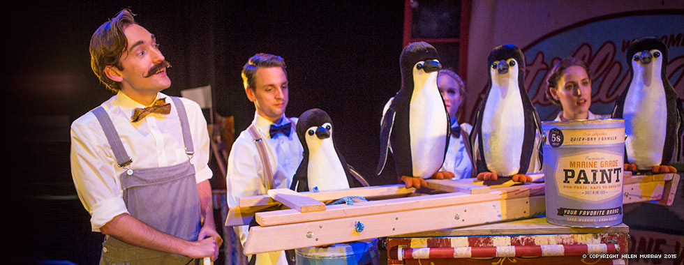 A man looks to his left at three people in assembly-line position while they paint stuffed penguins.
