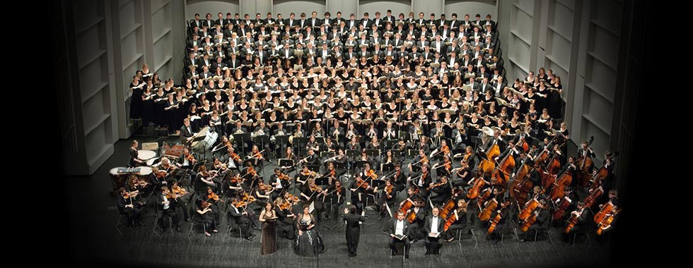 An orchestra and choir perform on stage.