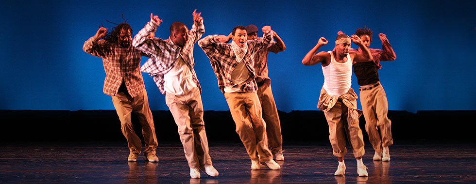 Six dancers wearing baggy pants and tank tops or plaid button-down shirts jump with both feet into a slanted position while they hold their arms up bent at the elbow.