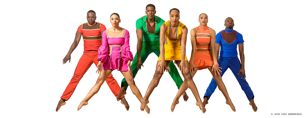 Six dancers, three men in pantsuits and women in miniskirted dresses, jump up with their legs straight and feet pointed down in an inverted V while they extend their arms straight down.