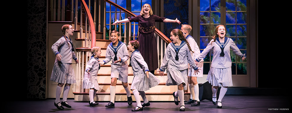 Maria sings out upon the foot of the staircase with her arms stretched-out wide, as the von Trapp children dance together in front of her.