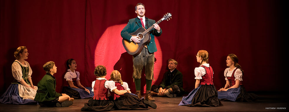 Captain von Trapp stands proudly as he plays his guitar while singing among Maria and his children who are sitting in a circle around him.