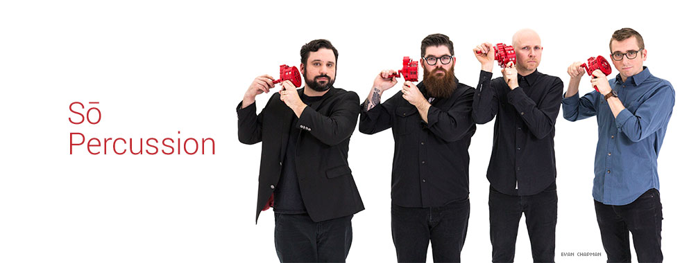 Each of the four members of So Percussion hold with both hands a crank-style noisemaker up to their right ear.