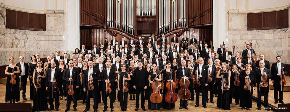 Warsaw Philharmonic Orchestra musicians hold their classical instruments while posing for an official portrait in an elegant music hall.