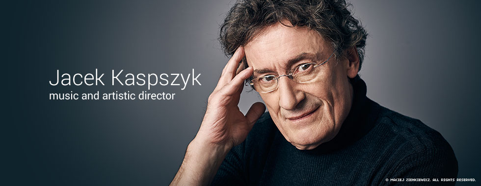 Warsaw Philharmonic Orchestra Music and Artistic Director Jacek Kaspszyk holds his hand to his forehead and looks at the camera in an official portrait.
