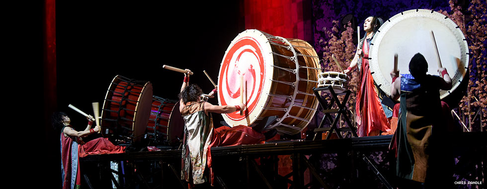 Three musicians play large drums set on their side on a platform while a fourth performer stands on the platform and plays a smaller drum.