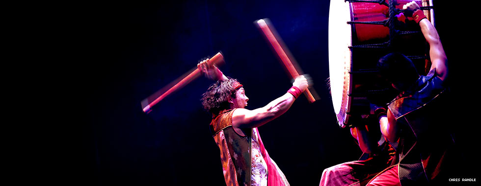 A percussionist with two drumsticks bangs on a large drum held upright by two men.