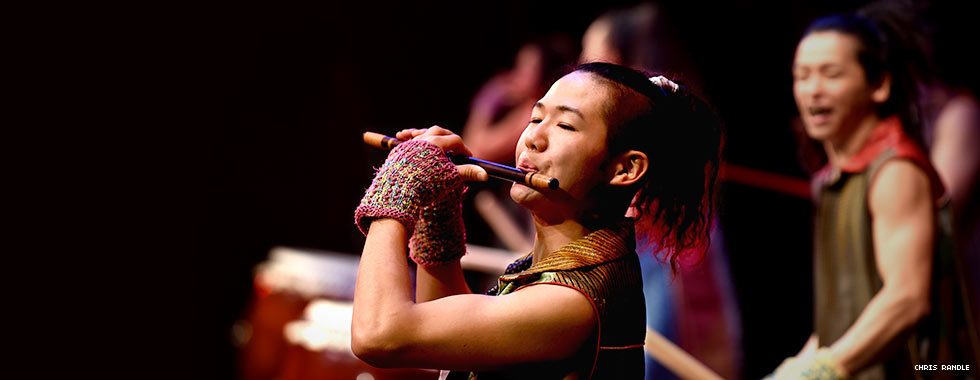 A musician plays the flute while drummers in the background look on.